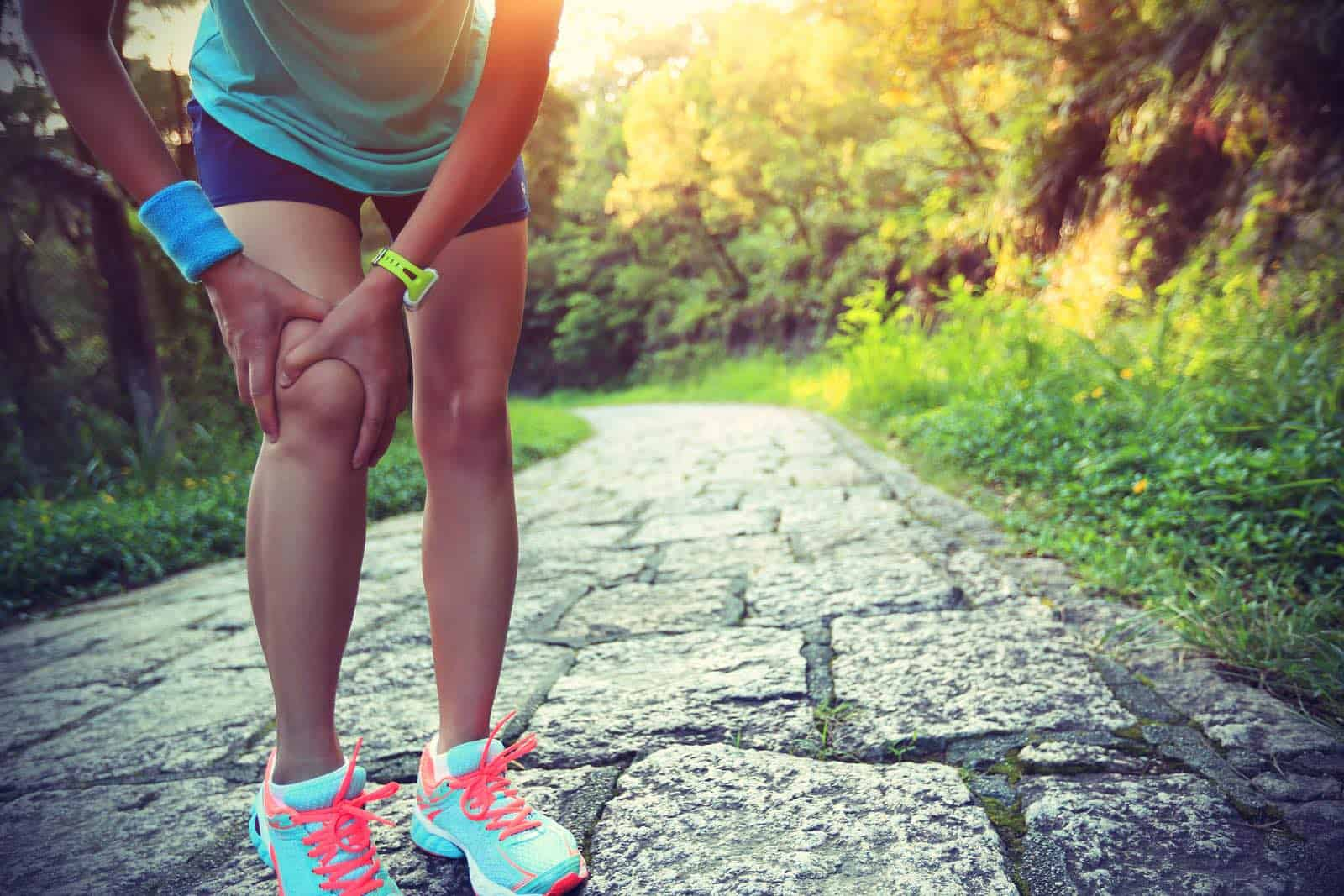 A woman runner holds her injured knee
