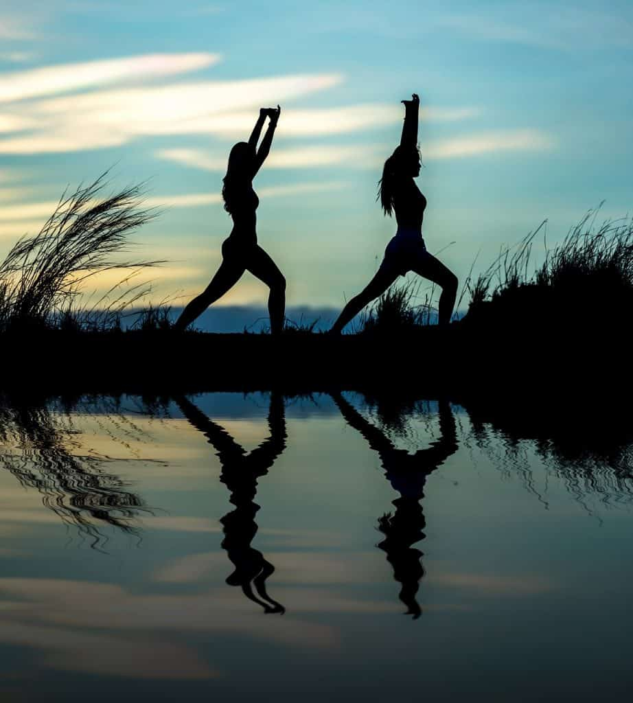 two people doing yoga pose by lake